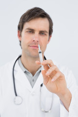 Portrait of a handsome male doctor holding an injection