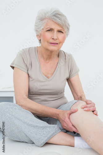 Senior woman with painful knee sitting on examination table