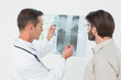 Male doctor explaining spine x-ray to patient