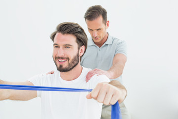Male therapist assisting a smiling man with exercises
