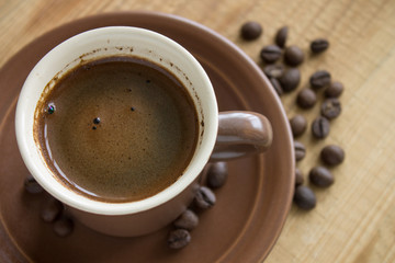 Cup of Coffee with beans on wood background