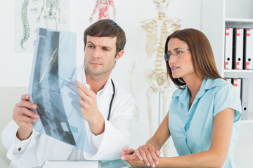 Male doctor explaining spinex-ray to female patient