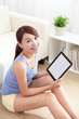 happy woman using tablet pc on sofa