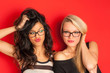 Funny blonde and brunette women portrait against red background.