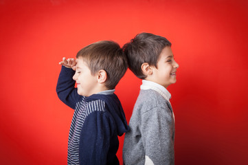 Young brothers funny portrait against red background.