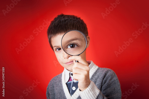 Child looking through a magnifying glass against red background.