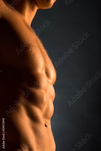 Close up of beautiful muscular male body in golden light
