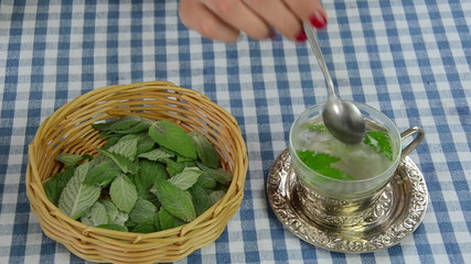 Hand put mint leaves from wicker dish to glass cup with water
