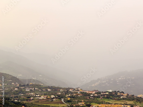 Village in mountain valley fog hides. Sicily, Italy. Time Lapse
