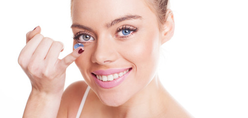 Beautiful woman inserting a contact lens