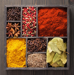 spices in box: pink and black pepper, paprika powder, curry, bay