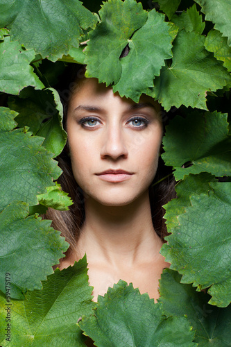 Portrait of young beautiful women in leafs