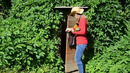 Farmer girl walk from basement house with preserve food jar pot
