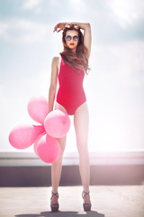 Beautiful happy girl with red balloons on the roof