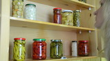 woman puts jars pickled red peppers tomatoes in cupboard shelves