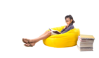 Young Malay Asian girl reading a book on a yellow bean bag