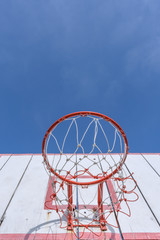 Basketball hoop against the warm summer sky