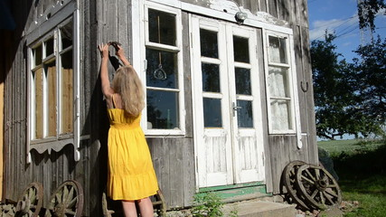 Woman in yellow dress hammering horse shoe on country house wall