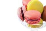 Colorful macaroons in vase on white background