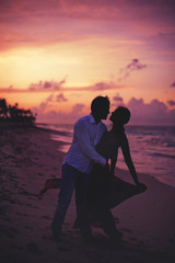 Beautiful couple on the beach during sunset