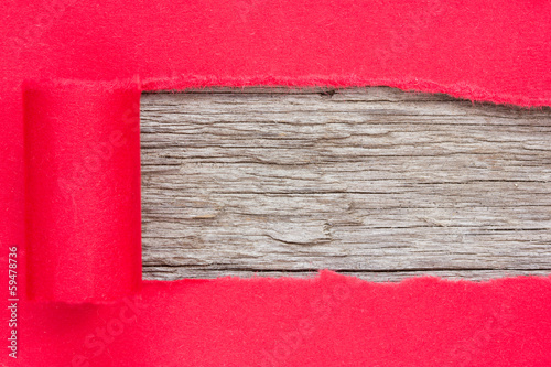 Red paper torn to reveal wooden panel