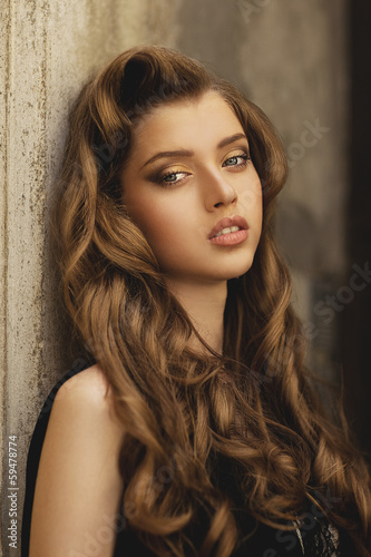 Portrait of elegant woman with curly hairstyle in black dress