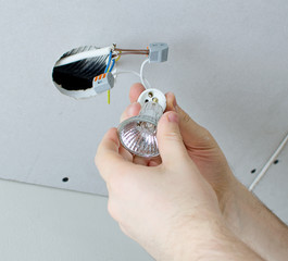 Male hands installing socket for light bulb