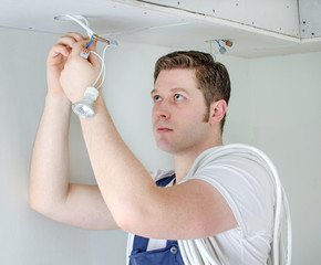 Certified electrician installing socket for light bulb
