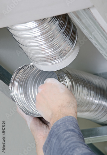 Male hands setting up ventilation system indoors