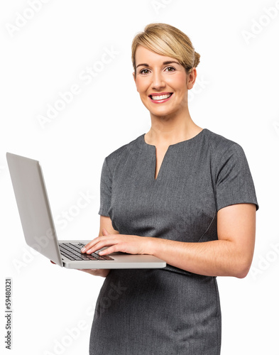 Portrait Of Happy Businesswoman Using Laptop