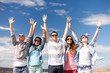 group of smiling teenagers holding hands up