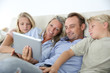 Family in couch websurfing with tablet