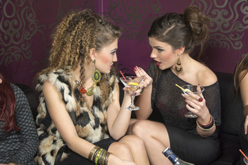 Portrait of two women talking to each other in night club