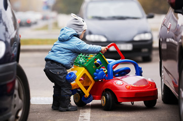 boy on parking with shopping carriage