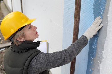 Construction inspector examine insulation of house facade wall
