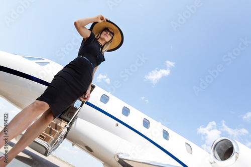 Woman In Elegant Dress Standing Against Private Jet - 59484122