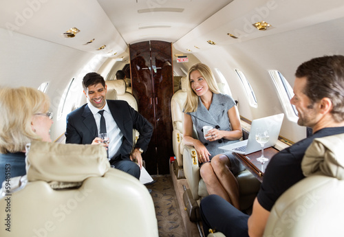 Business Professionals Having Drinks On Private Jet - 59485153
