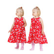 two identical twin girls in red dresses looking