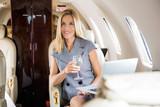 Fototapety Businesswoman Having Wine In Corporate Jet