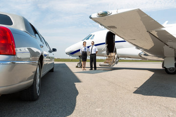 Airhostess And Pilot Standing Neat Limousine And Private Jet