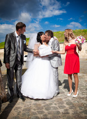 riends holding white isolated board in front of kissing couple