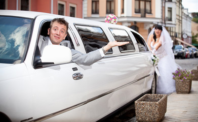 Handsome groom sitting in car while bride pushing it