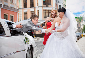 laughing bride and bridesmaid pulling young groom out of car