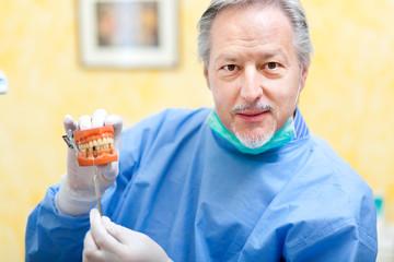 Dentist holding a denture