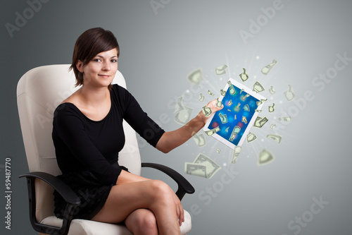 young woman holding tablet with money