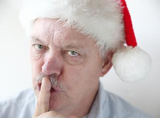 man in Santa hat asks for quiet