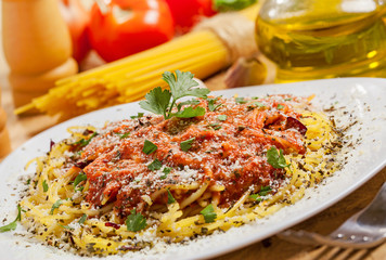 Pasta with sauce and parmesan cheese, ingredients on background