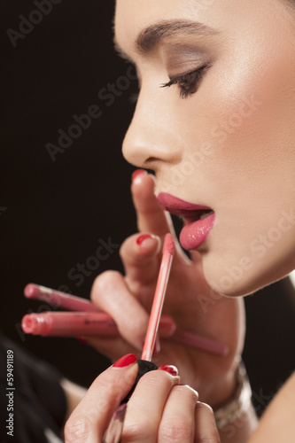 Applying lip-gloss to the lips of a young model