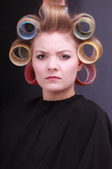 Unhappy blond girl hair curlers rollers by hairdresser in salon
