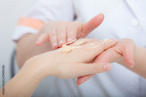 Beautician applying moisturizing cream on client hands spa